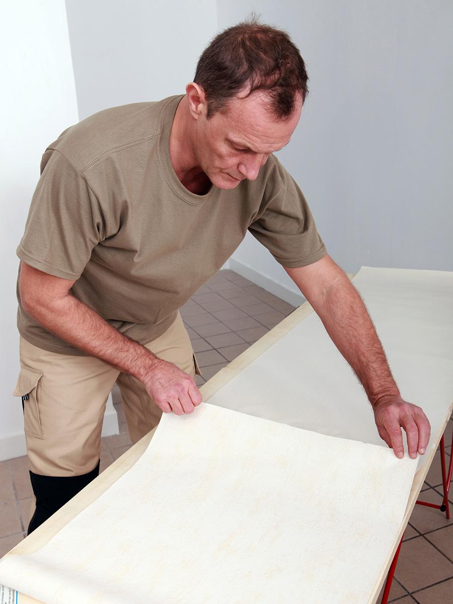 Tapezierarbeiten – Tapezierer zieht am Ende einer Tapete, die auf einem Tisch liegt – Talent Entrümpelung