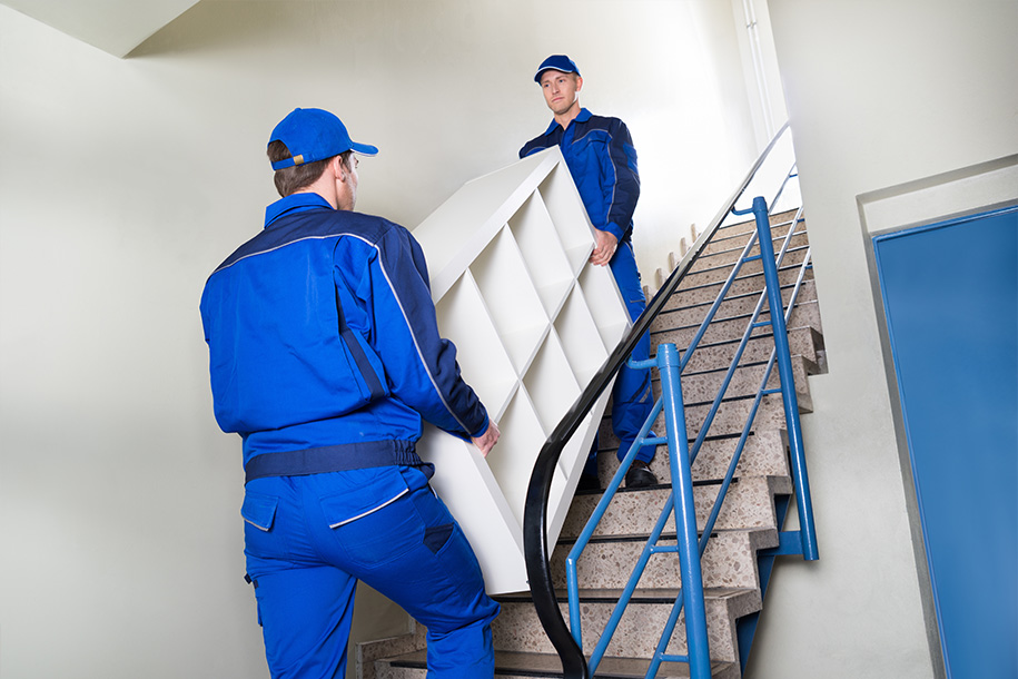 Entrümpelung – Arbeiter tragen einen Schrank über eine Treppe – Talent Entrümpelung