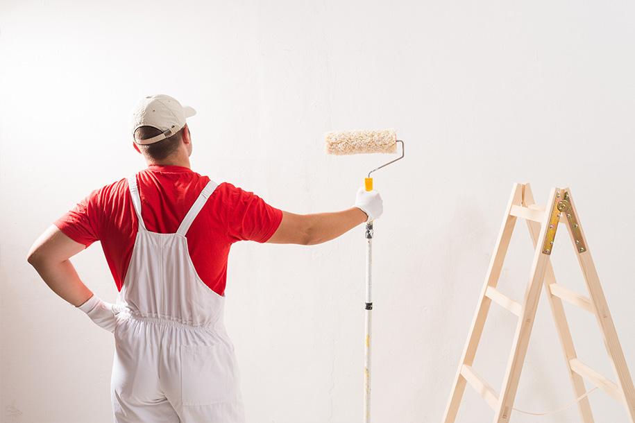 Maler hält eine Farbrolle und sieht auf eine unbestrichene Wand – Talent Entrümpelung