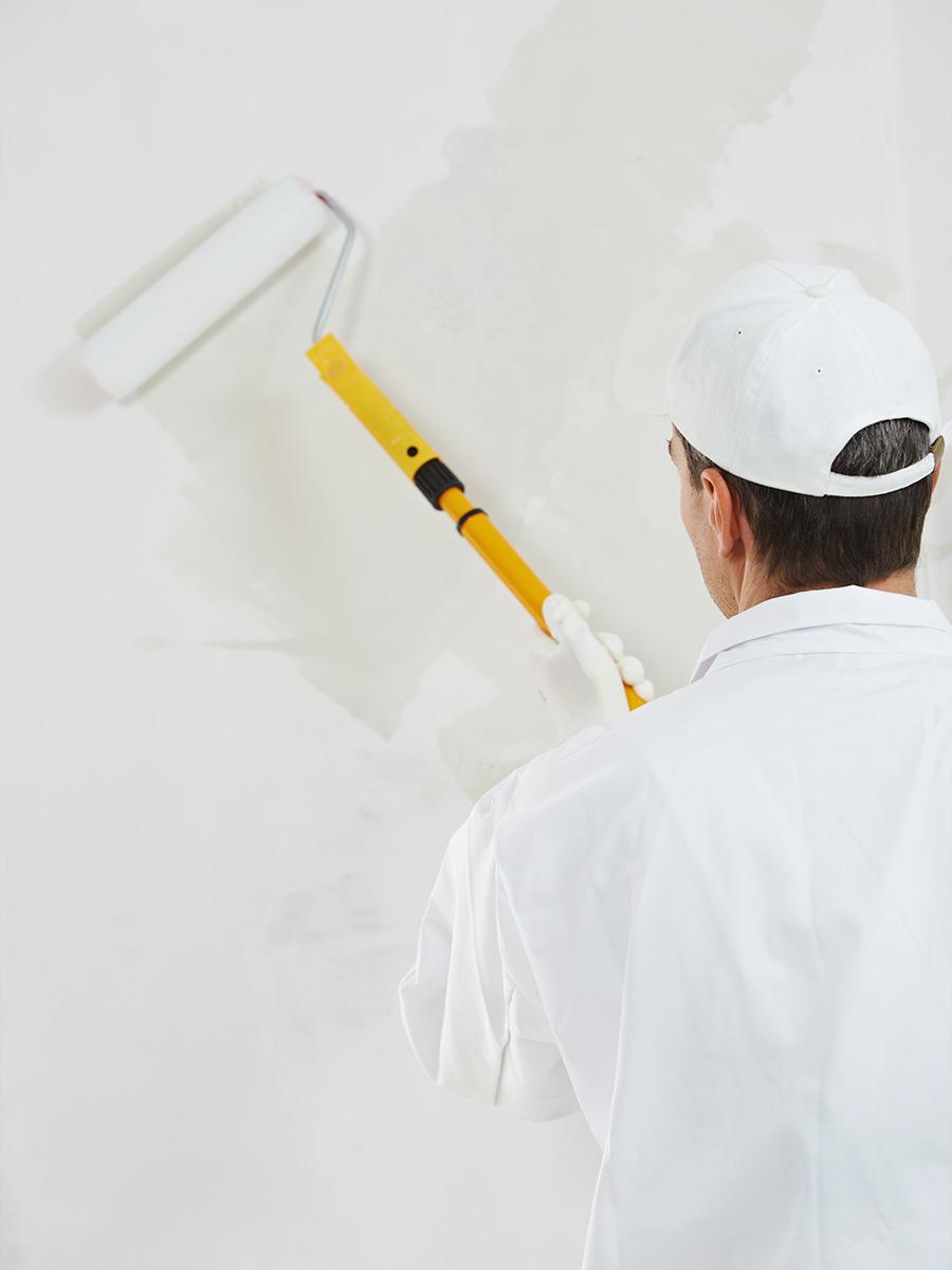Streicharbeiten – Maler streich eine Wand mit einer langen Farbrolle – Talent Entrümpelung