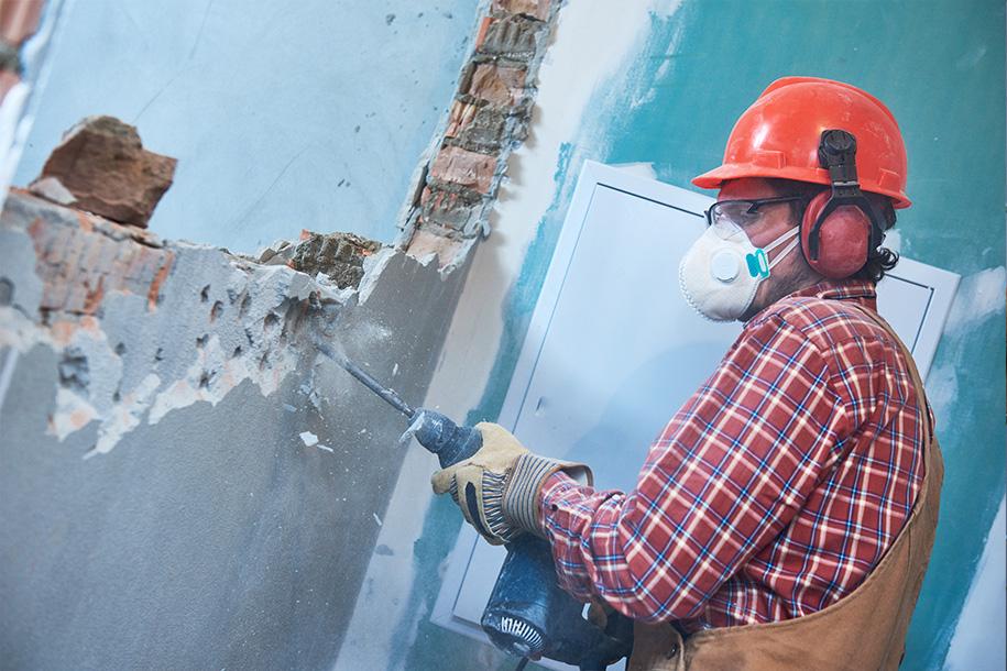 Abrissarbeiten – Arbeiter reißt mit einem Presslufthammer eine Wand ein – Talent Entrümpelung