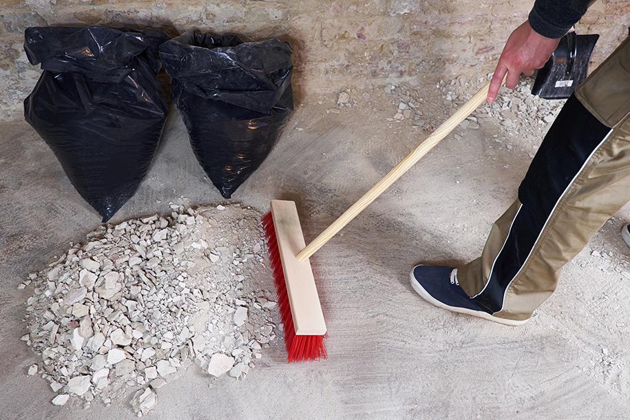Reinigungsarbeiten – Arbeiter fegt Schutt zu einem Haufen – Talent Entrümpelung