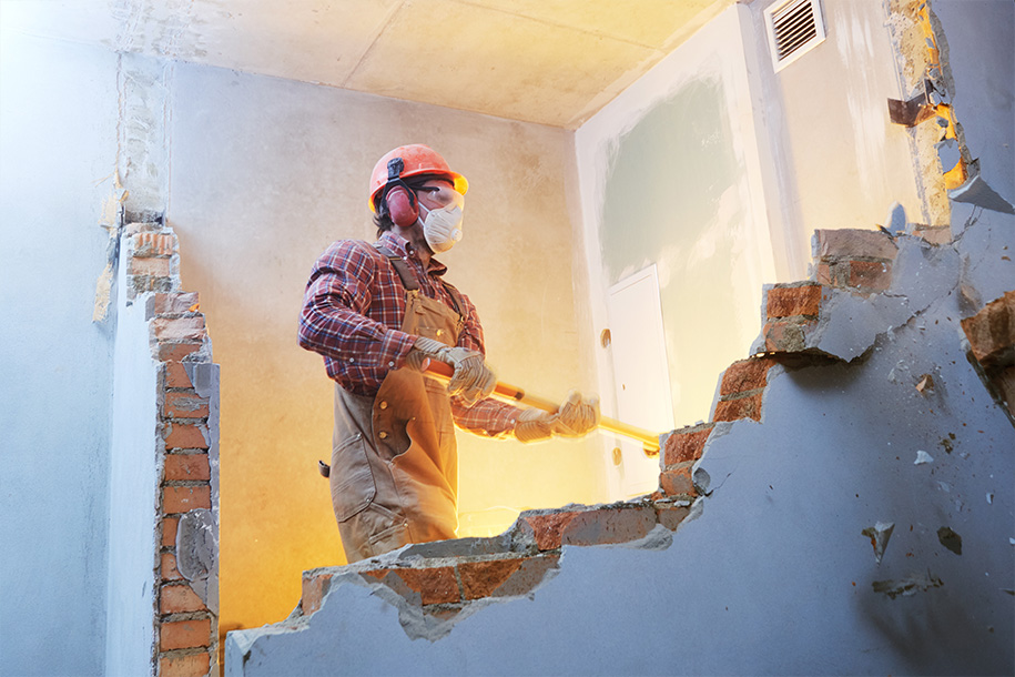 Abrissarbeiten – Arbeiter reißt mit einem Vorschlaghammer eine Wand ein – Talent Entrümpelung