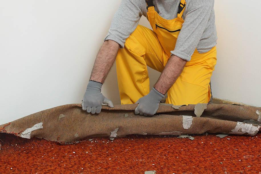 Wohnungsauflöser – Arbeiter entfernt einen Teppich vom Boden – Talent Entrümpelung