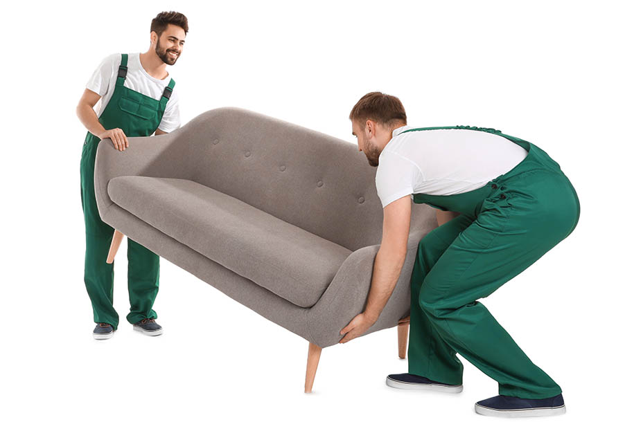 Entrümpelung Haushaltsauflösung – Entrümpler mit Arbeitslatzhosen tragen einen alten Sofa – Talent Entrümpelung